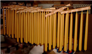 early american beeswax hand dipped candles hanging on a rack